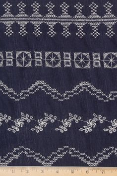 A gauze-like rayon crepe fabric with white embroidery set against a navy blue background.