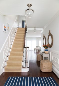 Cottage foyer boasts a traditional staircase clad in wainscoting lined with a bound sisal runner indoor outdoor by Sacco Sisal Stair Runner, Staircase Runner, Stair Runners, Navy Stair Runner, Traditional Staircase, Tapis Design, Coastal Living Rooms, Style Deco, Foyer Decorating