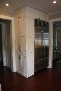 doors beside built-in, fridge side cabinet, fridge in corner, white kitchen cabinets, wood floor