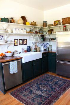 open shelving, farmhouse sink, vintage rug, dark cabinetry