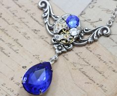 Gorgeous & unique necklace. Steampunk necklace using a vintage watch movement (non-working) and a vintage sapphire blue jewel.