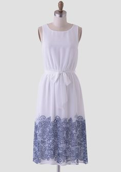 Ideal for a summer gathering or a semi-formal soiree, this white midi dress is adorned with a blue floral-lace print at the hem. Accented with an optional self-tie sash and an elastic waistband ...