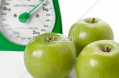 green apples and a scale - Green apples with a weighing scale at the background.