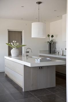 palest matt wood against pure white, polished slate (?) floor tiles and simple country elements in this contemporary kitchen