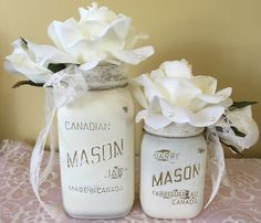 Nice mason jars with pretty cream flowers with pearls and lace ribbons