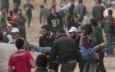 Israel's Lieberman blames Hamas over Gaza deaths - April 21, 2018.  Palestinian protesters evacuate a wounded youth during clashes with Israeli troops along Gaza's border with Israel, east of Khan Younis, Gaza Strip, Friday, April 20, 2018. Thousands of Palestinians joined the fourth weekly protest on Gaza's border with Israel on Friday, some burning tires or flying kites with flaming rags dangling from their tails. Two Palestinians were killed by Israeli troops...