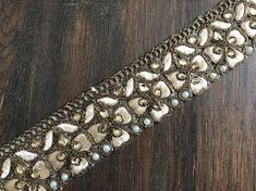 Measurements : 1.4 wide 1 Yard Copperish Gold Antique look Embroidered Trim Golden Ribbon Kundan and Pearls studded cut work embroidered Ribbon Sari Border with Traditional Indian Designs on Beige Organza Fabric. Art Quilts Fabric Trim Sari Fabric Trim Indian Fabric trim By The