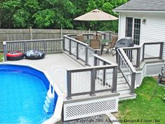 This is a great set up: separate area for grilling and a patio table near the house with steps to the yard and a gate to the pool. Also, gray deck boards with white railing reminds me of the beach