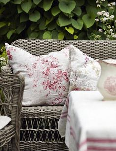 Gray wicker furniture with red and white throw pillows