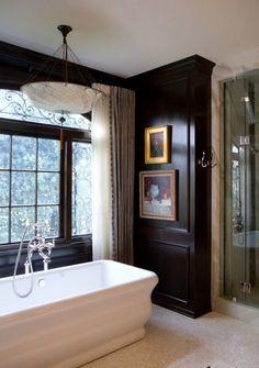 Glamorous bath with glossy black paneled walls, elegant chandelier and freestanding bathtub by the window.