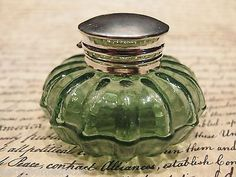 """Charming 2 1/4"""" High x 3 1/4"""" wide Charming Reproduction antique green glass inkwell. Very heavy thick glass each with charming subtle signs of being hand made. The hinged shiny lid is nickel plated b"""