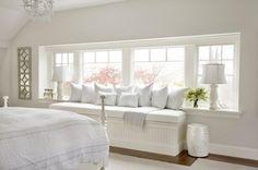 Sitzbank am Fenster mit vielen Kissen