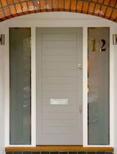 This subtle grey-sky coloured door is the epitome of contemporary chic. Front Door Porch, Porch Doors, Front Door Entrance, House Front Door, Windows And Doors, Porch Entry, Contemporary Front Doors, Modern Front Door, Porch Extension