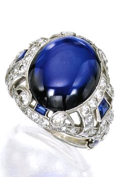 PLATINUM, SAPPHIRE AND DIAMOND RING Centered by a cabochon sapphire weighing approximately 9.54 carats, the openwork mounting set with round and single-cut diamonds weighing approximately 1.65 carats, further accented by four calibré-cut sapphires, size 6, partially numbered 163; circa 1925.