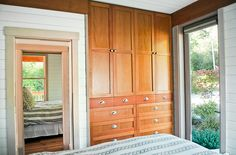 Love the storage built into the bedroom wall. It's a much more efficient use of space in a tiny bedroom than a standard closet. holly-beach-cottage-3