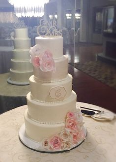 Blush and ivory wedding cake.  Edible, wafer paper roses. Gold cake topper and edible monogrammed plaque