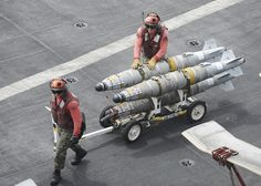 "U.S. 5TH FLEET AREA OF RESPONSIBILITY (Aug. 15, 2013) Cpl. William Gilbert, from Greeley, Colo., left, and Sgt. Benjamin Narez, from Saugus, Calif., assigned to the ""Death Rattlers"" of Marine Fighter Attack Squadron (VMFA) 323 transport bombs on the flight deck of the aircraft carrier USS Nimitz (CVN 68). (U.S. Navy photo by Mass Communication Specialist 3rd Class Chris Bartlett/Released) Military Jets, Military Aircraft, Fighter Pilot, Fighter Jets, Navy Chief Petty Officer, Uss Nimitz, Us Navy Ships, F-14 Tomcat, Navy Aircraft"