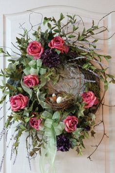 Beautiful wreath with pink roses, bird nest, mint ribbon and greenery