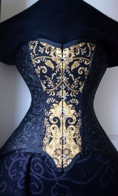 the intricate patterns and inlay on her corset gave it the appearance of a gilded, carved door