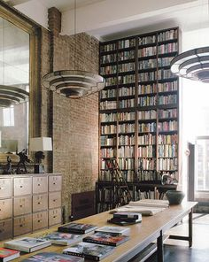parede de tijolos aparentes + estante + iluminação + teto alto