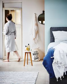 bedroom with a light blue wall and a grey boxspring bed, a hammam towel, soap, a leather rug and a laundry basket | Styling Fietje Bruijn, Marianne Luning, Frans Uyterlinde | vtwonen june 2015 | #vtwonenshop