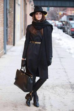 a woman wearing black boots, black pants, black coat and a sexy hat. She looks very pretty