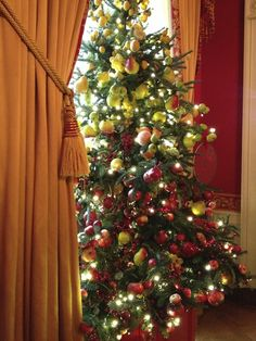 A Christmas tree covered in red and yellow fruit in The Red Room at @The White House.  #whsocial