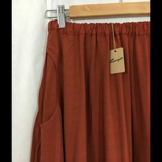 """CP Shades Claudia Rayon Skirt (s) Lightweight rayon skirt is midi length. Color on tag says """"brick"""", but it's a burnt orange color. Two hip pockets. Beautiful drape! Elastic waist, pull on style. Nothing could be more easy, breezy! 100% Rayon, machine wash. Made in USA! No trades. (Note: Last photo is to show how it looks on) CP Shades Skirts Midi"""