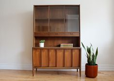 Versatile MCM cabinet by Keller Furniture.    Top features sliding glass with adjustable shelf. One long slim drawer with dividers. Hidden storage below. Walnut with formica countertop for extr...