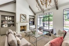 Sophisticated living room features vaulted ceiling adorned with taupe beams over fireplace topped with Louis Philippe Mirror in Gold flanked by alcoves filled with taupe built-ins accented with decor and flatscreen TV.