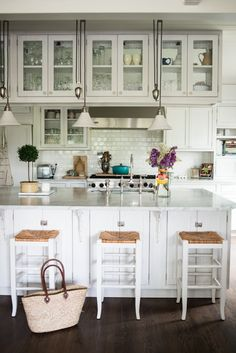 This kitchen is amazing! Love the stools, the lighting, the cupboards, and the backsplash! #kitchen