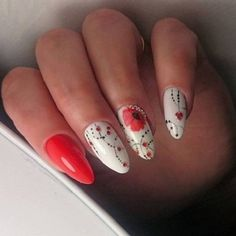 The Red Spring Nail Art. Color-ify your spring with this great combo of white, red and black on your nails. Simply add red flowers and black dots on white base and embellish it up with red studs to give it presentable look for spring season.