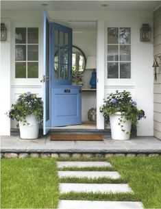 A brown doormat is placed on slate pavers between white planters as a blue dutch front door is fitted behind a blue storm door and between sidelights. Exterior Paint, Exterior Design, Slate Pavers, White Planters, Galvanized Planters, Dutch Door, White Farmhouse, Front Door Decor, Porch Decorating