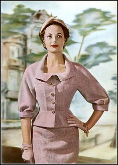 Model in rose wool suit, short jacket with rounded and curved collar is worn over a slightly flaring skirt, by Jean Dessès, photo by Georges Saad, 1954