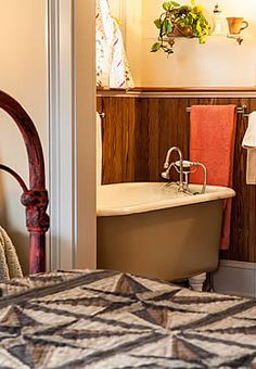 Sumac Room A large bed made with a grey patterned quilt, facing into a bathroom with a clawfoot tub.