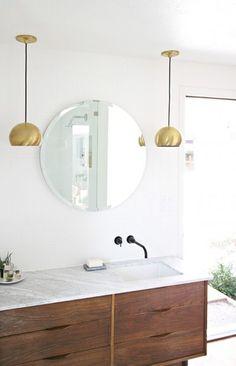 Mid-Century style bathroom with a round vanity mirror, designed by Kristen Grove, via @sarahsarna.