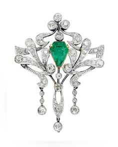 An Antique Emerald and Diamond Pendant, circa 1905  The openwork plaque centering a shield-shaped emerald weighing approximately 2.35 carats, amid old mine-cut floral and foliate scrolls and tassels, mounted in platinum and 18k gold