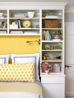Utilize the space around the head of your bed for storage. Configure shelves and cabinets to suit your storage needs. Here, a lower cabinet has a flat table surface that serves as a nightstand, and plenty of shelves keep books, bedtime necessities, and decorative objects.