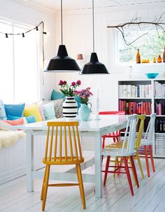 """A series of painted dining chairs, colour-coordinated books and paste-coloured cushions bright a bright and friendly atmosphere to this Norwegian dining room."" @Bright.Bazaar /"