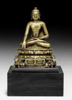 A BRONZE FIGURE OF BUDDHA SHAKYAMUNI ON A LION THRONE. Northeastern India, Pala, 8th/9th c. Height 16.5 cm. Silver and copper inlays. Bronze mit Silber- und Kupfereinlagen. Der historische Buddha sitzt im Diamantsitz auf einem doppelten Lotospodest mit versetzt angeordneten Blättern. Dieses ruht auf einem quaderförmigen Thron, der in den Ecken von vier Löwen gestützt wird (simhasana). Ein Tuch fällt in doppelter Falte auf allen vier Seiten über den Rand. Das Mönchsgewand ist glatt anliegend…