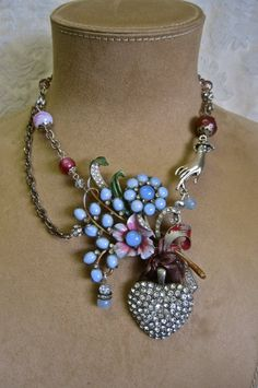 I decided to make this vintage 40s huge floral brooch into an even more special and stunning statement. A delicate silver hand reaches down to hold the gorgeous enamel bouquet. I added a 40s rhinestone heart and several vintage glass and crystal beads. A shabby chic ribbon holds the
