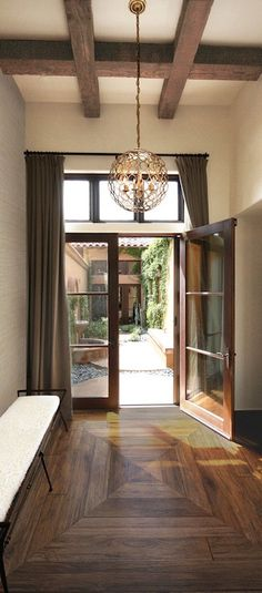 Elegant foyer features wood ceiling beams accented with a Currey & Company Tartufo Chandelier hanging over a wood and iron bench atop concentric wood floors placed in front of windows stacked over glass double doors dressed in chocolate brown curtains.
