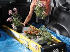 Keep your car clean. Do some light prep in your car on your way to the nursery. Line your trunk (or wherever your plants will be going into) with a tarp. Over the tarp place a ladder. The ladder rungs are the perfect place for plants and flowers to sit and not flop over a spill everywhere. It's like little seats for all of your plants.