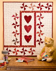 "Got a stash of red scraps? Combine Pinwheel blocks with appliquéd hearts in a quick quilt that's perfect for Valentine's Day—or any day! ""Three of Hearts"" by Ellen Pahl."