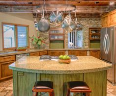 Rustic Mod - The wood stain, countertops and island in the kitchen match colors in the ceiling and flagstone floor.