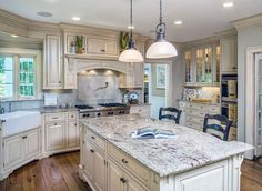 Country kitchen with off white cabinets, bianco antico granite and farmhouse sink