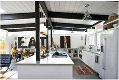 Une grande cuisine avec îlot ouverte sur un salon style scandinave. Façades des meubles blanche , le sol est dans le même gris pastel que le plan de travai