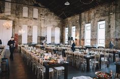 This raw warehouse venue is equipped with farm tables, bistro lighting, a bar, and even some lounge seating - Brainerd, Minnesota | Photo: Adam Kennedy Photography