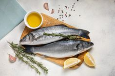 Fresh sea bass fish and ingredients for cooking, lemon and rosemary. white background top view. #paid, , #Sponsored, #Ad, #fish, #Fresh, #sea, #ingredients Baked Sea Bass, Baked Fish, Giant Shrimp, Dorado Fish, Rustic Background, White Dishes, Fresh Seafood, Grilled Salmon, Bass Fishing