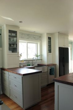 this is the first kitchen where I have liked two toned cabinets (don't love the black fridge :( and not really a fan of marble) It almost makes me want wood counters too.....  Paint is Pewter Tankard by Sherwin Williams